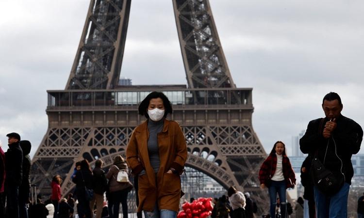 Một phụ nữ đeo khẩu trang phòng dịch giữa những người không có dụng cụ bảo hộ tại tháp Eiffel, Paris. Ảnh: Reuters.