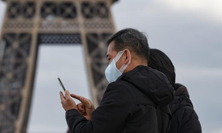 Du khách đeo khẩu trang phòng dịch ở thủ đô Paris của Pháp hôm 14/3. Ảnh: AFP.