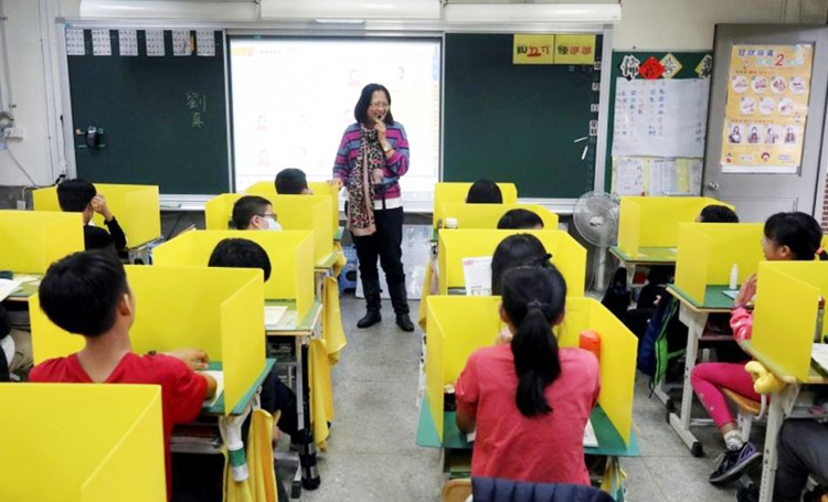 Học sinh trường tiểu học Đại Giáp, Đài Loan, ngồi ăn sau vách ngăn màu vàng ngày 13/3 để phòng Covid-19. Ảnh: Reuters.
