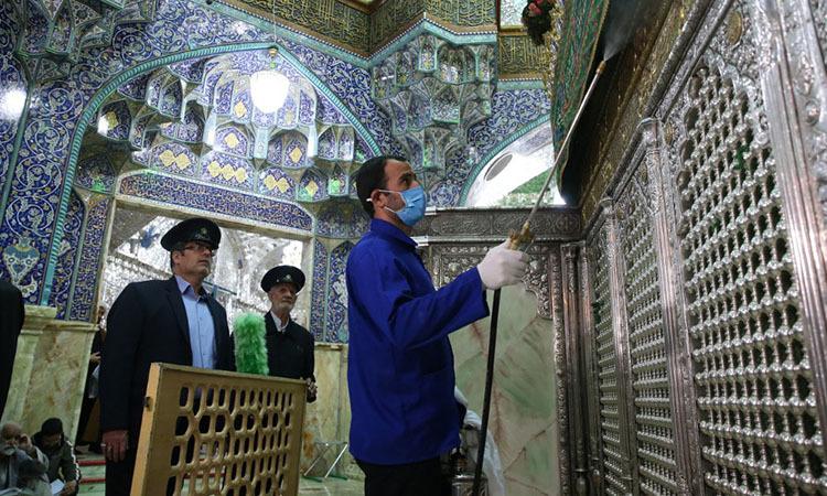 Nhân viên vệ sinh khử trùng đền thờ Masumeh ở thành phố Qom, Iran hôm 25/2. Ảnh: AFP.