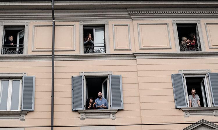 Người dân cổ vũ đội ngũ y bác sĩ từ ban công tại Milan, Italy hôm 14/3. Ảnh: NY Times.