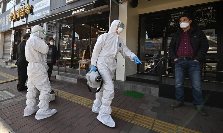Nhân viên y tế mặc đồ bảo hộ trắng phun hóa chất tẩy trùng tại khu vực quanh nhà thờ Grace River ở Seongnam ngày 16/3. Ảnh: AFP.