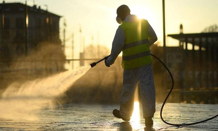 Công nhân khử trùng đường phố ở Milan, Italy hôm 13/3. Ảnh: Reuters.
