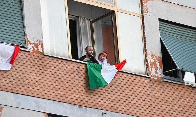 Hai người dân đứng trên ban công ở Magliana, thành phố Rome, Italy hôm 15/3. Ảnh: AFP.