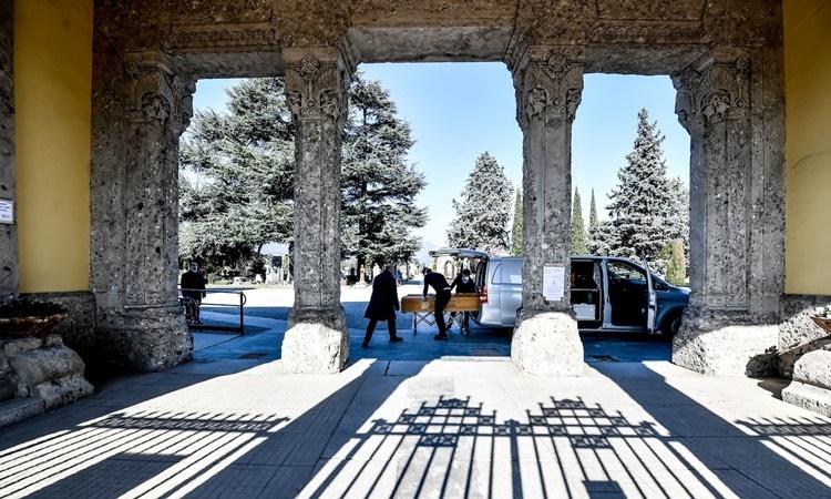 Nhân viên tang lễ chuyển quan tài ra khỏi một xe tang tại nghĩa trang Bergamo ngày 9/3. Ảnh: AP.