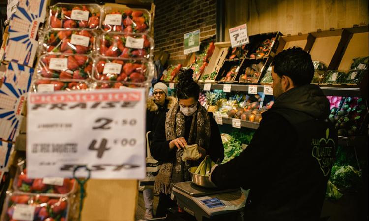 Người phụ nữ đeo khẩu trang mua rau quả tại một cửa hàng ở Paris, Pháp hôm 16/3. Ảnh: NY Times.