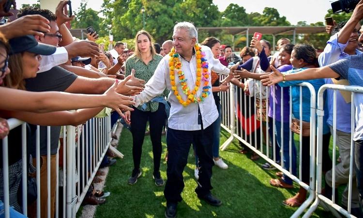Tổng thống Mexico Andres Manuel Lopez Obrador bắt tay với những người ủng hộ khi đến thăm một thị trấn ở Xochistlahuaca hôm 14/3. Ảnh: Reuters.
