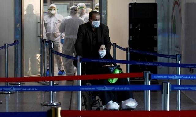 Hành khách đi từ Iran đến sân bay Najaf ở Iraq ngày 5/3. Ảnh: Reuters.