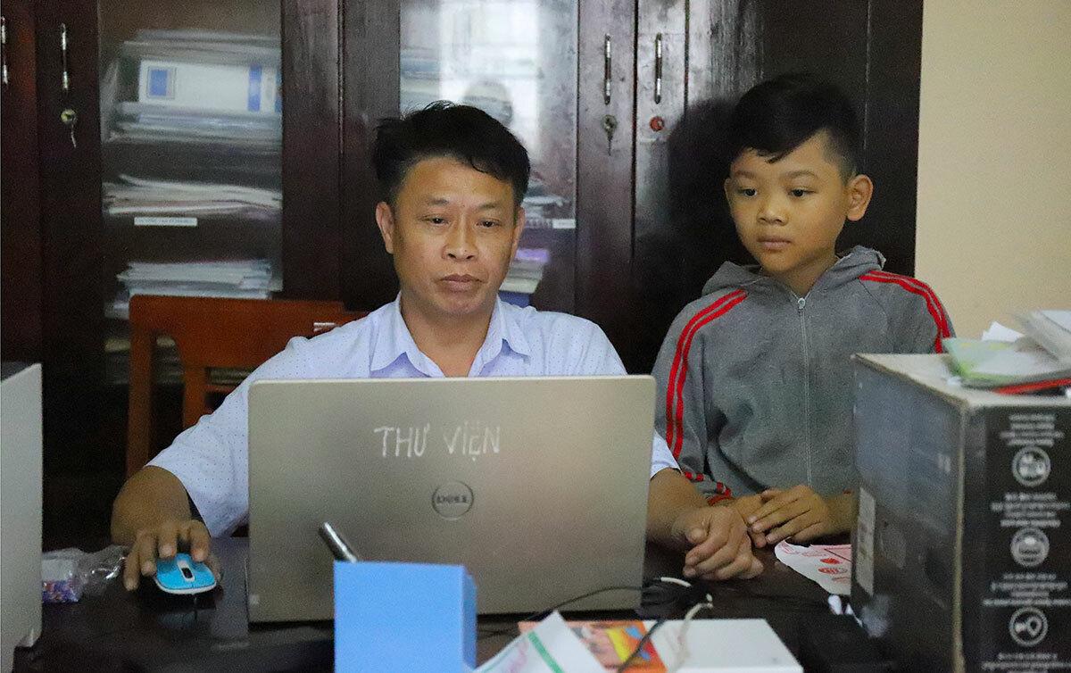Thầy Tú mở máy tính in phiếu ôn bài cho em Nguyễn Tiến Dũng (áo xám), học sinh lớp 4 vào sáng 18/3. Ảnh: Đức Hùng