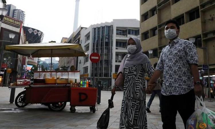 Người dân đeo khẩu trang trên đường phố Malaysia hôm 6/3. Ảnh: Reuters.