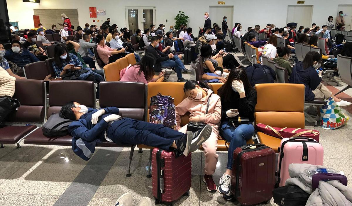 Cả trăm người về từ các nước Châu Âu sáng 18/3 đang chờ ở nhà ga T2 để về khu cách ly tập trung.Ảnh: Giang Huy