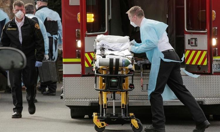 Nhân viên y tế di chuyển cáng để chuẩn bị đưa một bệnh nhân nhiễm nCoV lên xe cứu thương ở Kirkland, Washington, ngày 5/3. Ảnh: Reuters.