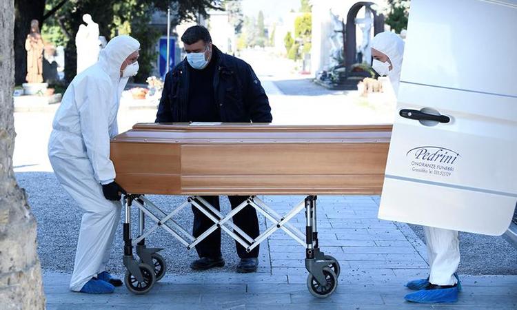 Người đàn ông đeo khẩu trang vận chuyển quan tài người chết vì Covid-19 đến nghĩa trang Bergamo, Italy hôm 16/3. Ảnh: Reuters.