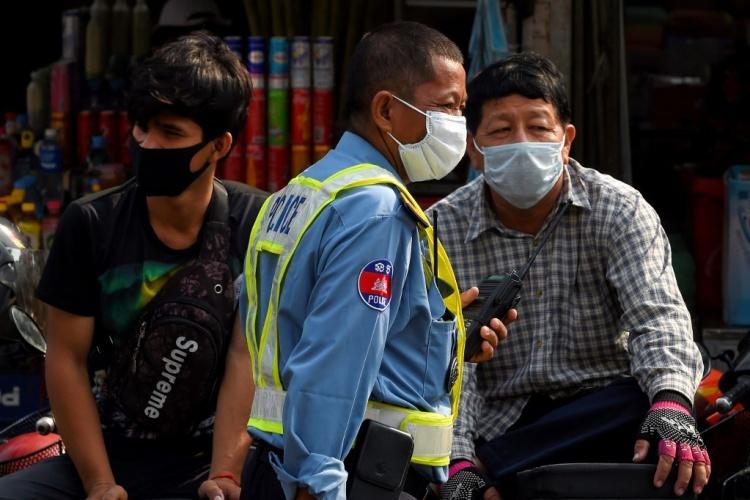 Người dân và cảnh sát Campuchia đeo khẩu trang chống Covid-19 tại một khu chợ của Phnompenh ngày 17/3. Ảnh: AFP.