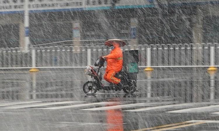 Một công nhân vệ sinh băng qua đường giữa trời tuyết rơi ở Vũ Hán ngày 15/2. Ảnh: Frontier Post.