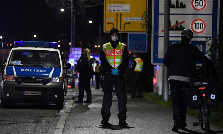 Một cảnh sát Đức đứng gác tại khu vực kiểm soát phương tiện giữa thành phố Kehl, Đức và Strasbourg, Pháp ngày 12/3. Ảnh: AFP.