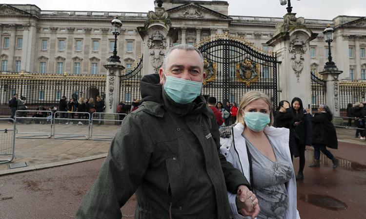 Cặp vợ chồng đeo khẩu trang bên ngoài Cung điện Buckingham, London hôm 14/3. Ảnh: AP.