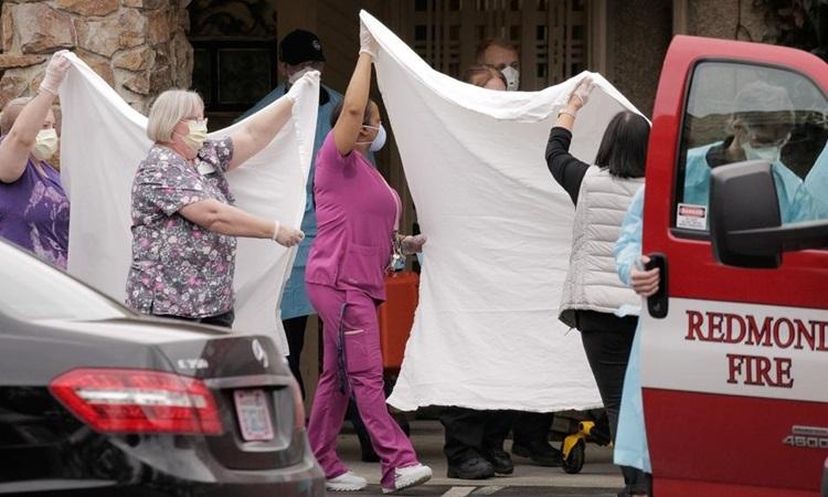 Nhân viên y tế Mỹ chuyển bệnh nhân nhiễm nCoV lên xe cứu thương tại bang Washington hôm 1/3. Ảnh: Reuters.