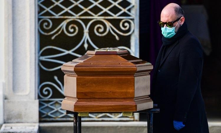 Người đàn ông đeo khẩu trang đứng cạnh quan tài mẹ chết vì nhiễm nCoV trong lễ tang gần phốBergamo, Lombardy hôm 20/3. Ảnh:AFP.