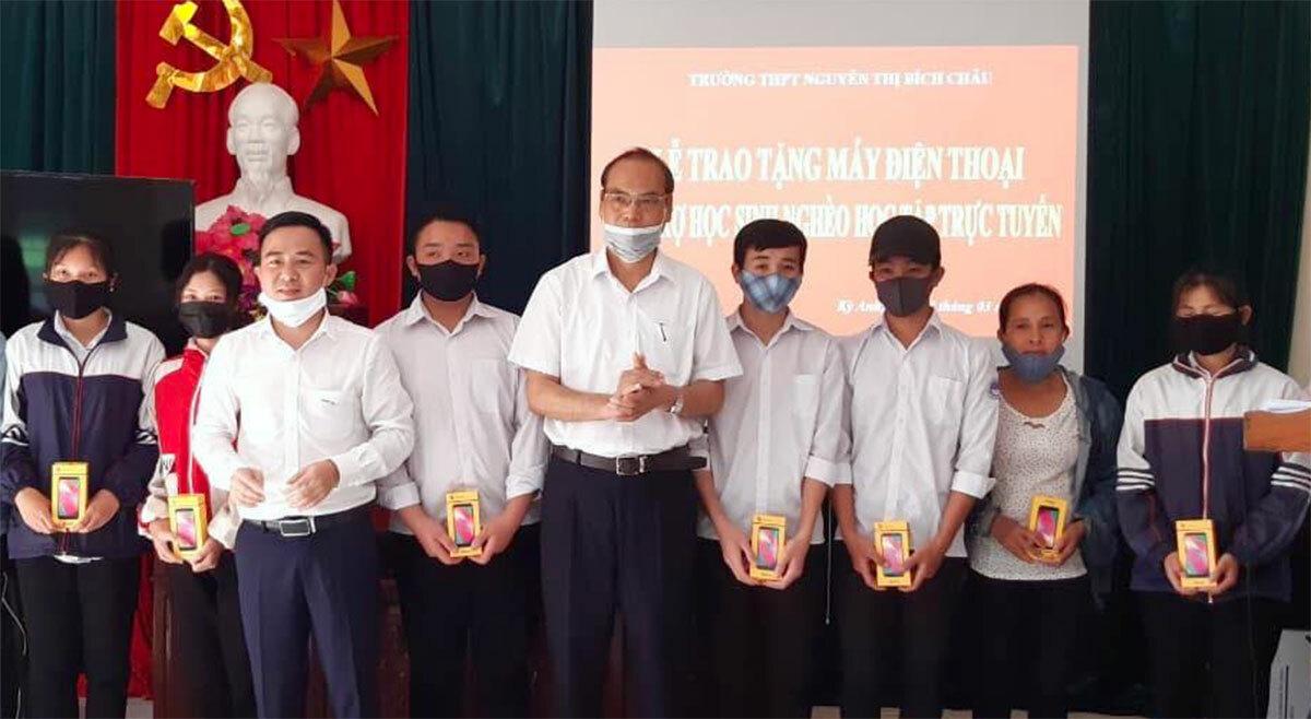 Thầy Dương Đình Thọ (thứ 5 từ phải qua) cùng lãnh đạo nhà trường trao điện thoại cho học sinh nghèo chiều 23/3. Ảnh: Đình Thọ