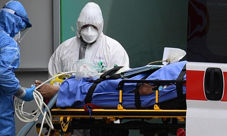 Nhân viên y tế đưa bệnh nhân vào khu hồi sức tích cực tại một bệnh viện ở Milan hôm 23/3. Ảnh: AFP.