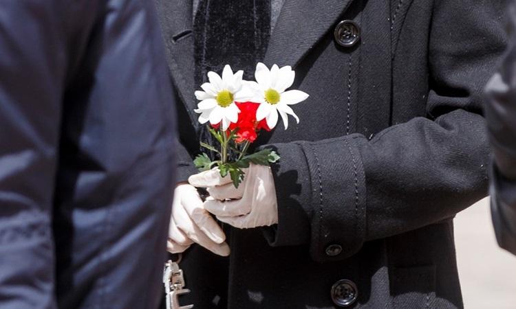 Người đàn ông cầm hoa trong tang lễ của bệnh nhân Covid-19 tại Madrid, Tây Ban Nha hôm 23/3. Ảnh: AFP.