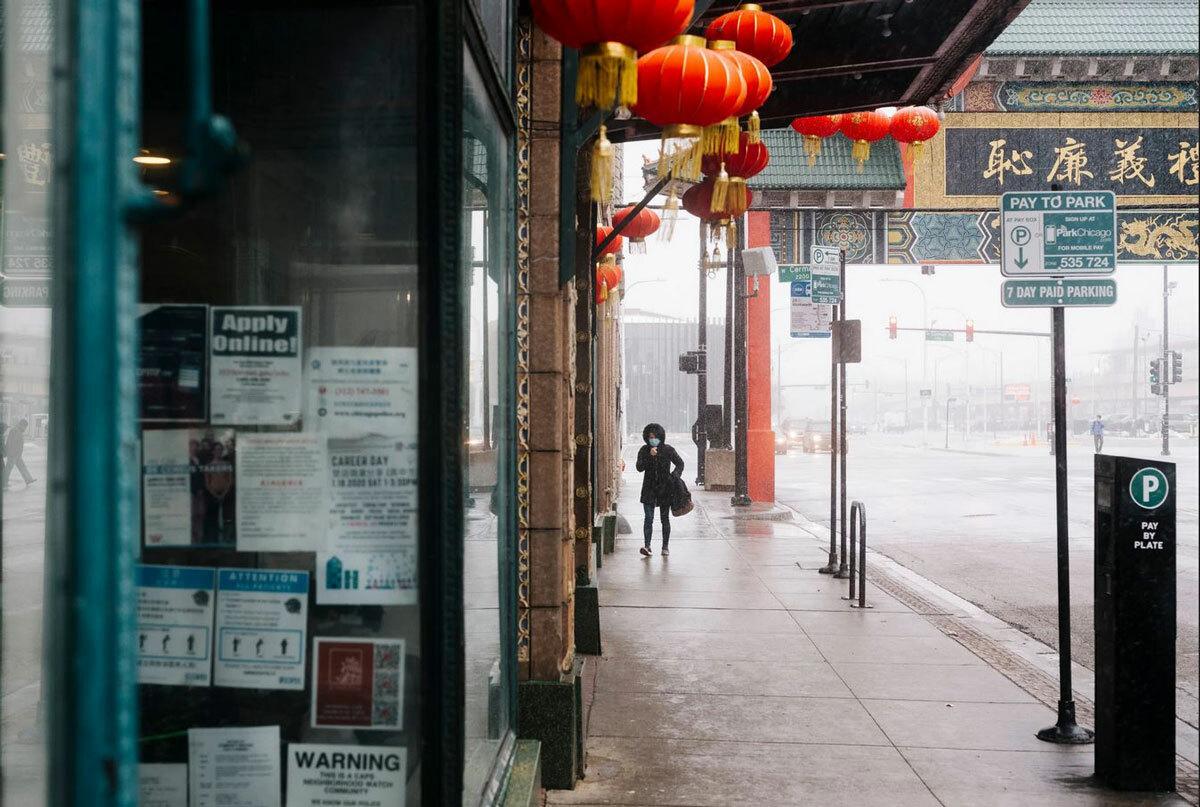 Người phụ nữ đeo khẩu trang đi bộ một mình trên phố người Hoa ở thành phố Chicago, bang Illinois. Ảnh: NY Times.