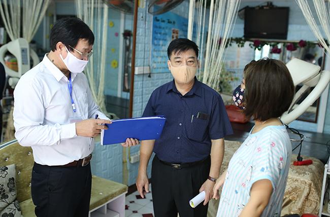 Cán bộ phường Vĩnh Tuy (Hai Bà Trưng) vận động một cửa hàng cắt tóc Yên Lạc dừng hoạt động. Ảnh: Tất Định