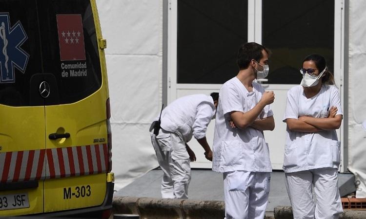 Hai nhân viên y tế trò chuyện cạnh xe cứu thương bên ngoài bệnh viện La Paz ở Madrid hôm 23/3. Ảnh: AFP.