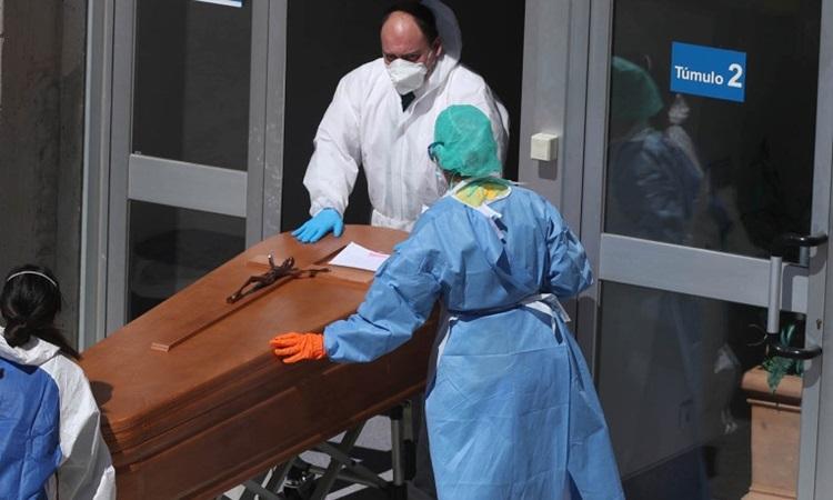 Nhân viên tang lễ di chuyển quan tài bệnh nhân Covid-10 tại bệnh việnSevero Ochoa ở Madrid hôm 25/3. Ảnh: Reuters.