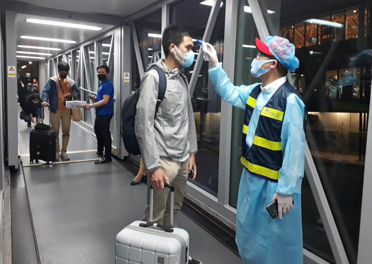 Từng hành khách được kiểm tra sức khỏe trước khi lên máy bay. Ảnh:NVCC.