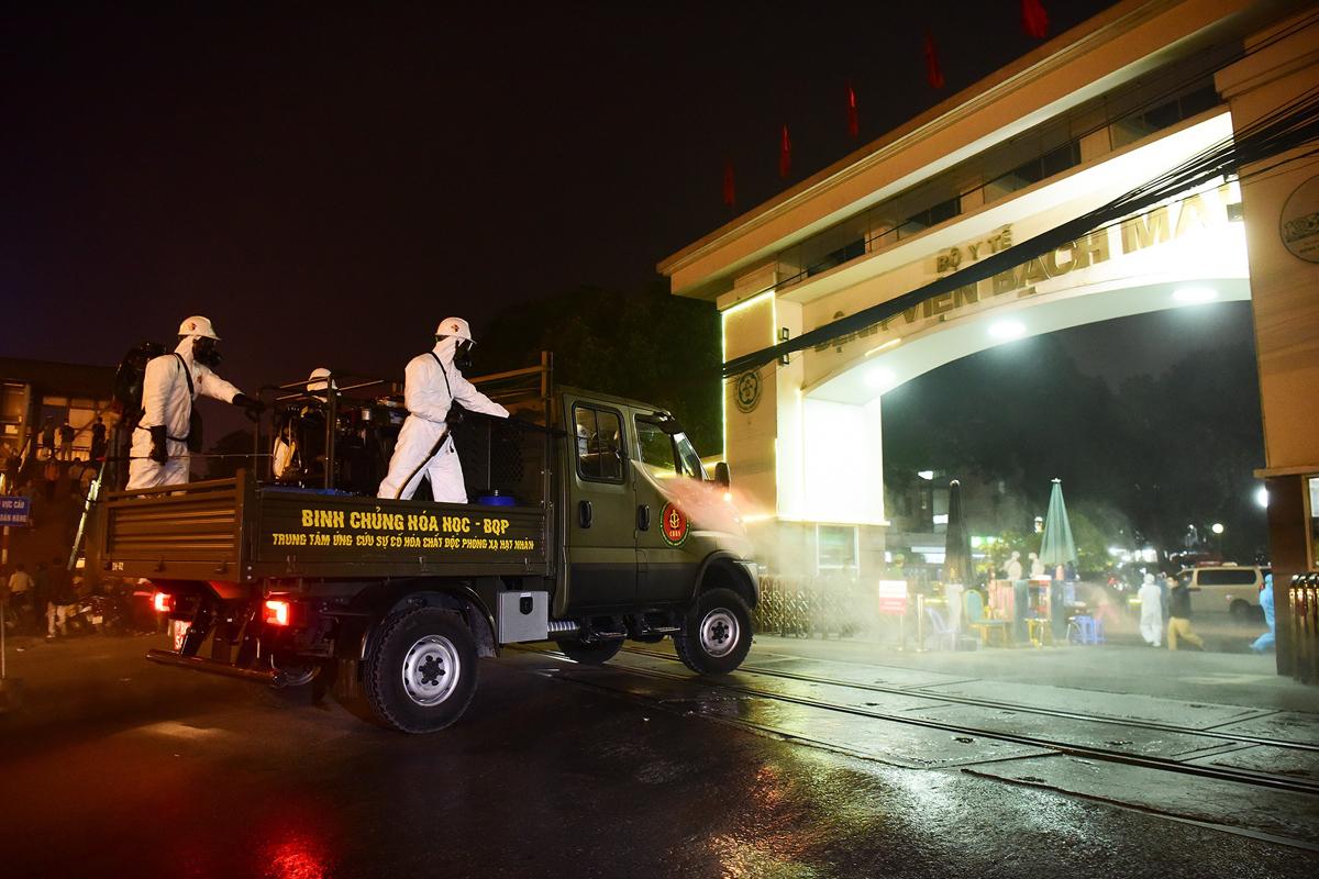 Lực lượng quân đội tổ chức phun khử trùng khu vực cổng viện Bạch Mai tối 28/3. Ảnh: Giang Huy.