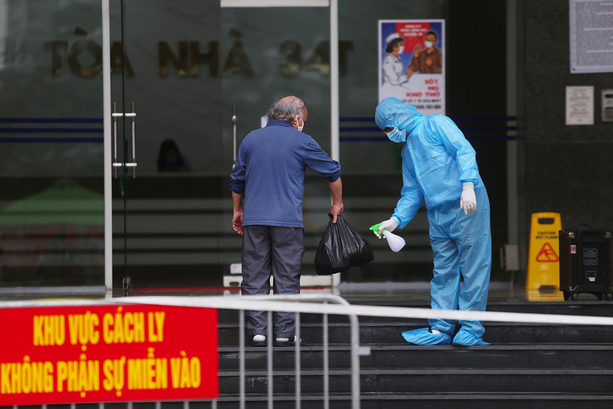 Nhân viên làm nhiệm vụ sát khuẩn đồ cho cư dân toà nhà. Ảnh: Phạm Dự.