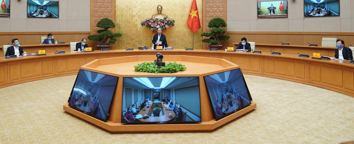 Cuộc họp thường trực Chính phủ chiều 30/3, các thành viên dự họp đều đeo khẩu trang và ngồi cách xa nhau; một số đại biểu dự họp qua đầu cầu trực tuyến. Ảnh: VGP
