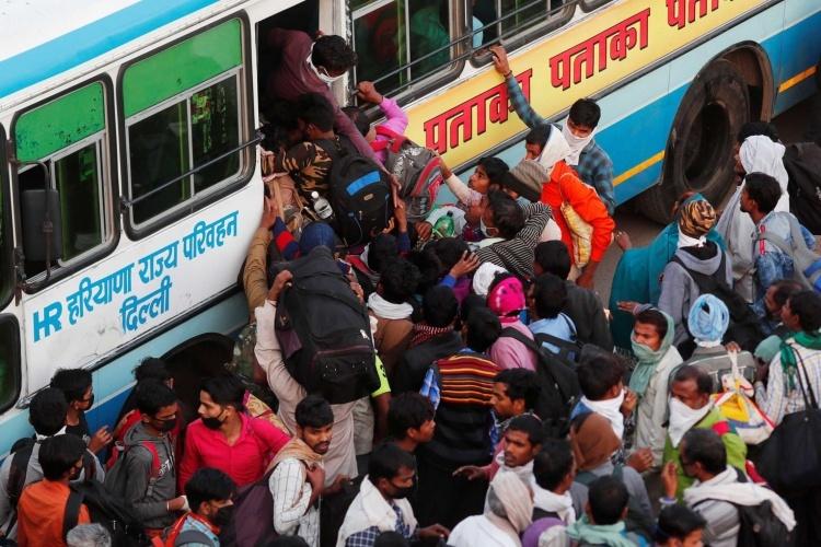 Người dân Ấn Độ chen chúc lên xe bus ở ngoại ô New Delhi,  ngày 29/3, để về quê sau lệnh phong toả. Ảnh: Reuters.
