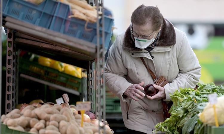 Một người dân Áo đeo khẩu trang khi mua hàng tại thủ đo Vienna. Ảnh: AFP.