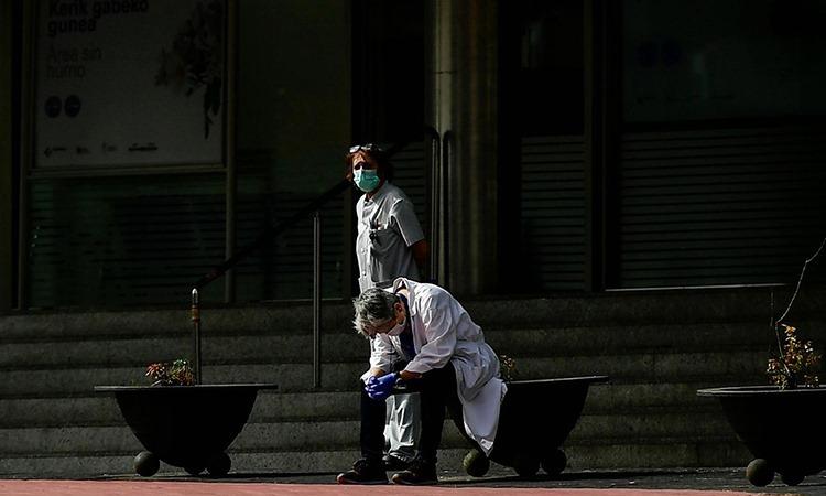 Nhân viên y tế ngồi bên ngoài Bệnh viện Txagorritxu, thành phố Vitoria, Tây Ban Nha hôm 20/3. Ảnh: AP.
