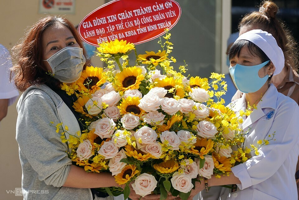 Bà Đặng Thị Lynh Trang (áo xám), bệnh nhân 34, tặng hoa cảm ơn đội ngũ y bác sĩ Bệnh viện Đa khoa Bình Thuận. Ảnh: Việt Quốc.