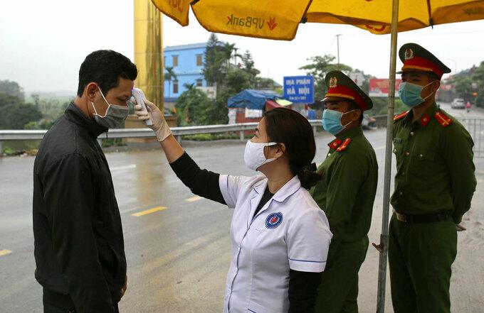 Nhân viên y tế đo thân nhiệt tại người ra vào Hà Nội, sáng 2/4. Ảnh:Tất Định
