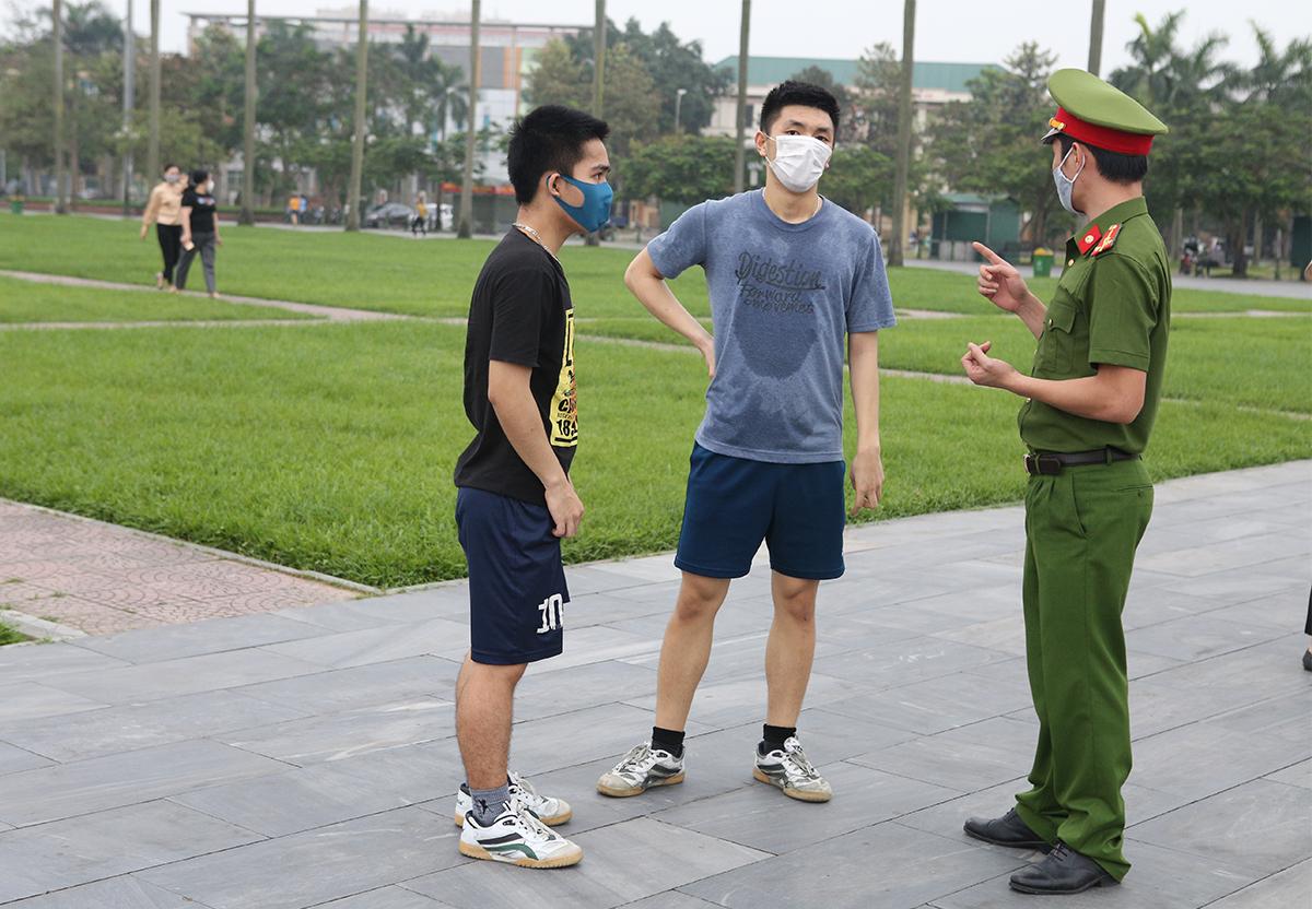 Cán bộ công an trực tiếp nhắc nhở những người chạy thể dục phải giải tán. Ảnh: Nguyễn Hải.