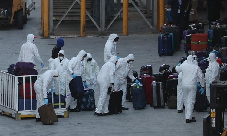 Công nhân mặc đồ bảo hộ kiểm tra hành lý trên từ du thuyền Hà Lan Zaadam sau khi nó cập cảng ở Florida, Mỹ hôm 2/4. Ảnh: AFP.