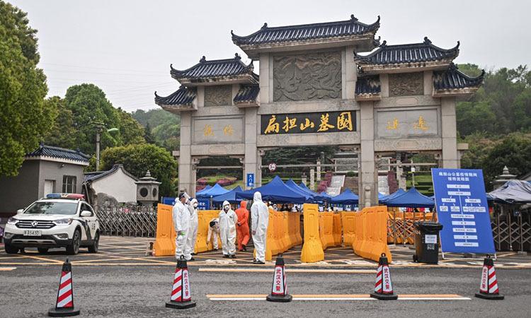 Những người mặc đồ bảo hộ tại lối vào nghĩa trangBiandanshan ở Vũ Hán, tỉnh Hồ Bắc, Trung Quốc hôm 31/3. Ảnh: AFP.