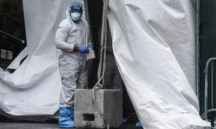 Một nhân viên y tế đến gần chiếc xe tải đông lạnh được dùng làm nơi chứa thi thể người chết vì nCoV bên ngoài Bệnh viện Trung tâm Brooklyn tại thành phố New York ngày 3/4. Ảnh: AFP.