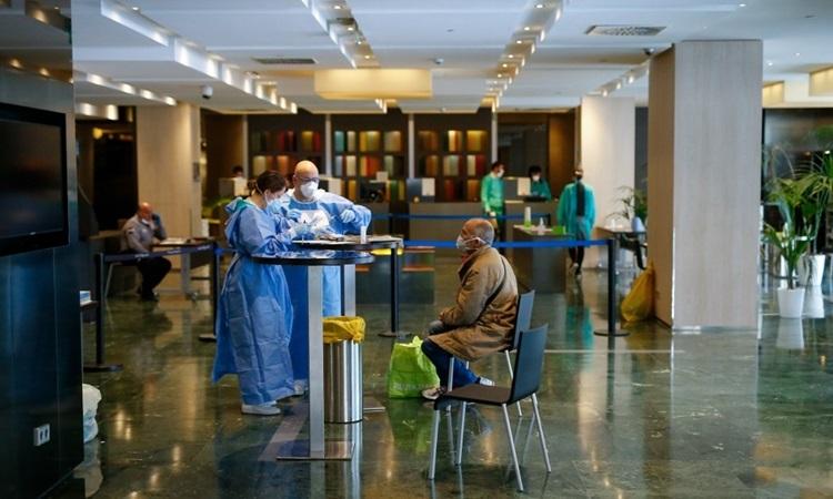 Nhân viên y tế tiếp đón bệnh nhân Covid-19 được chuyển đến khách sạn 5 saoMelia Sarria ởBarcelona hôm 2/4. Ảnh: AFP.