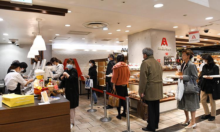 Người dân xếp hàng mua bánh mì tại cửa hàng ở Tokyo hôm 26/3. Ảnh: NYTimes.