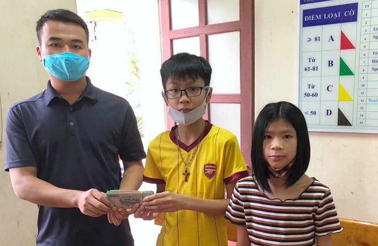 Hải (áo vàng) cùng em gái (bên phải) trao cọc tiền cho đại diện công an phường Nam Hà. Ảnh: Đ.H