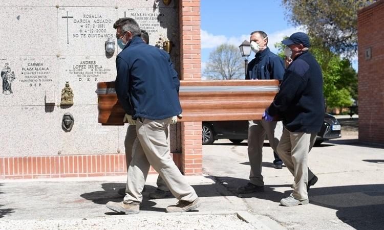 Nhân viên nhà tang lễ di chuyển quan tài chứa thi thể một bệnh nhân Covid-19 tại Madrid, Tây Ban Nha, ngày 4/4. Ảnh: AFP.