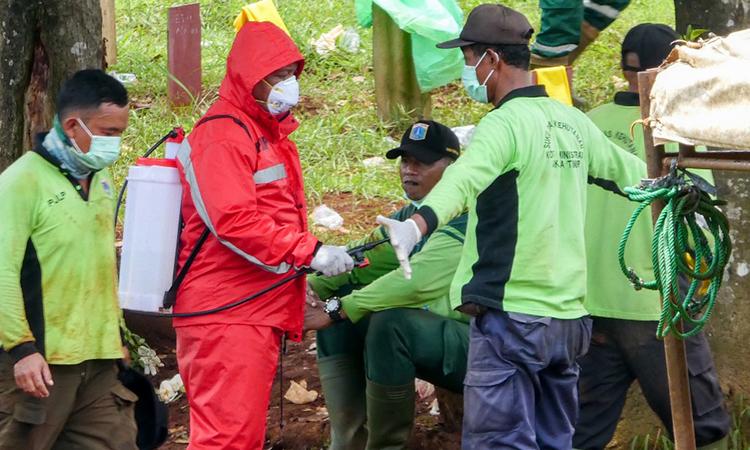 Nhân viên nhà tang lễ (áo xanh, đứng bên phải) được xịt hóa chất tẩy trùng khi chôn cất người chết vì nCoV tại Jakarta ngày 31/3. Ảnh: AFP.