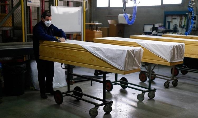 Nhân viên nhà tang lễ che phủ quan tài người chết do nCoV tại Barcelona, Tây Ban Nha hôm 3/4. Ảnh: AFP.