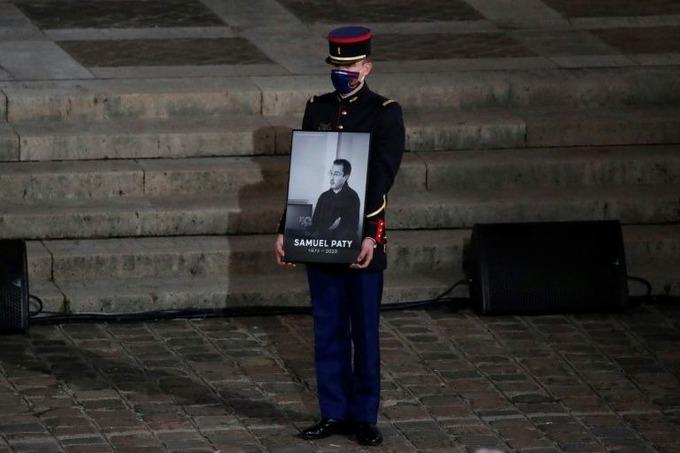 Một Vệ binh Cộng hòa Pháp cầm chân dung Samuel Paty trong buổi lễ tưởng niệm quốc gia thầy giáo Pháp bị chặt đầu tại Paris hôm 21/10. Ảnh: AFP.